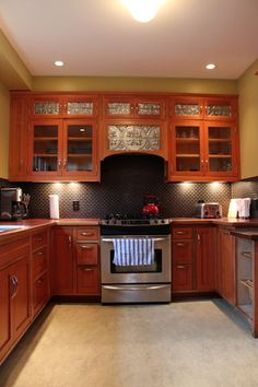This Sleek Kitchen replaces Cabinet Door panels with Antique Ceiling Tiles and Glass.