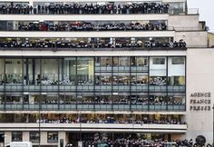 The staff of press agency Agence France-Presse lined up outside their headquarters holding...
