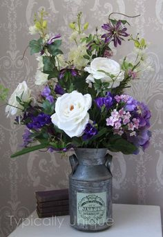 White roses and purple flowers in shabby chic urn