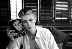 DAVID BOWIE'S TOP 100 BOOKS. Click here http://www.openbooktoronto.com/news/special_feature_how_read_bowie to see the list.  Photo: David Bowie with Buster Keaton Book, Los Angeles, 1975  © Steve Schapiro