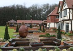 This is my dream! Tudor style home, with a square, copper finish firepit on my grounds to share with my fellow friends! #SharetheWarmth