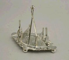 Antique silver-plated toast rack with divisions made of tennis racquets and nets.