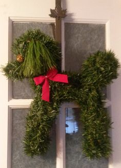 Poodle wreath of green pine with red trim by Arrangementsfloral