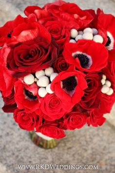 Close up shot of a spectacular RED bouquet using anemones, Black Magic roses, Freedom roses, Forever Young roses and silver Brunia Nodiflora