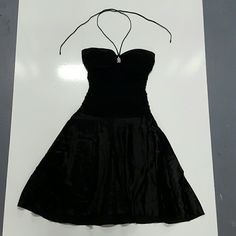 Classy black  sweet heart neck line with tie back Wonderful black classy a line dress with sweet heart neck line that has a rinstone detailed pendent in the center. The sides are sinched, and the top Ties for more support for the lightly padded top. The top is made of stretchy material and polyester and spandex. The skirt is a silky shiny rayon and acetate blend for a  smooth fabric. No snags stains or tears, this is in great condition. This is a siz3 5/6 B. Darlin Dresses