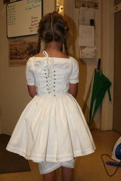 Little girl's underclothes back view. Her stays feature lacing just like an adults version but also have straps to keep the stays in place. The petticoats are so cute and puffy!