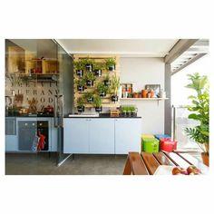 """""""Para criar um mesmo ambiente, integrar a cozinha estreita com a varanda continuamos a bancada com o mesmo material no tampo e acabamentos das portas. E pra esconder o aquecedor a gás uma horta deslizante."""" Mauricio Arruda Design"""
