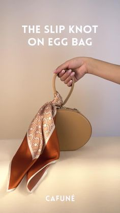 The Slip Knot exudes a casual yet confident vibe. Loop a printed scarf like the C-Lock Silk Scarf in Coral around an Egg Bag to add colour and character, and let the ends blow freely with the summer breeze. The cherry on top for your holiday. Scarf On Bag, Scarf Top, Diy Scarf, Ways To Wear A Scarf, How To Wear Scarves, Diy Clothes Life Hacks, Head Scarf Tying, Head Scarf Styles, Designer Scarves