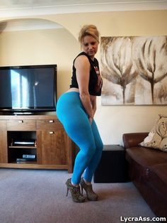 Curvy big butt woman in blue lycra leggings yoga pants and heels. Big hips and thighs in lycra tights.