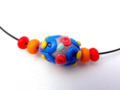 Multi-colored glass like bead made from clay by Marie Segal by mariesegal on Etsy