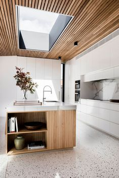 Beautiful modern white kitchen with wood accents and great skylight