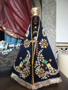 Imagem sacra de Nossa Senhora Aparecida, com manto na tonalidade azul, bordado em linha e cravejado de pedrarias, mãos em frente ao peito, sentido de oração, possue coroa dourada na cabeça.