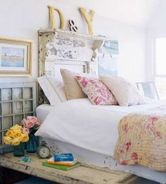 Flea Market Treasures:   Well-worn, comfortable pieces serve as the backbone of cottage decor. With that in mind, distressed doors form the base of this flea market chic platform bed, while an antique mantel, worn and weathered, serves as a headboard. Oversize letters form an impromptu monogram above the makeshift headboard.