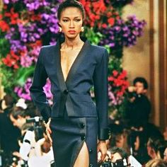 A model displays a navy blue barathea wawe jacket and long split skirt for Yves Saint-Laurent's