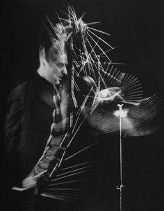 Drummer Gene Krupa performing on cymbals at Gjon Mili's studio.