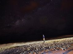 It looks like he is standing on the moon. It's actually the beach at Lake Malawi at night.