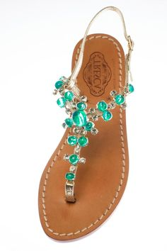 """Gemma is a gorgeous green and has gold Italian leather straps. Our soles are European sizes made in Italy. They are made from Italian leather with a wrapped, wooden heel.If you're a half size, size up. All of our Italian sandals are handmade to order by our cobbler in store. We keep true to the Capri sandal by using nails not glue. We offer a 1/2"""" flat as well as a 1"""" heel.Because each is unique and made-to-order, please allow up to 5 business days to ship. All custom shoes are final sale…"""