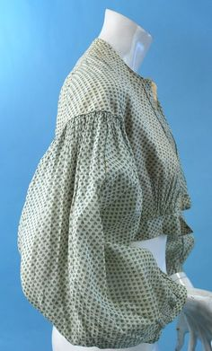 """Green Spring Print Blouse. Pleasing green sprig printed cotton voile, bodice only, dating to the 1860's With cotton inner bodice, exterior bodice closes with tinyest crochet button, piping thruout with dropped voluminous sleeves. In excellent uncleaned antique as found all original condition. Chest measures 32"""", waist 22"""", length from shoulders 15"""". Small collection out of Vermont estate"""