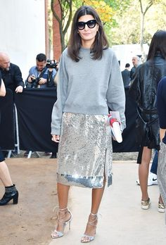 Giovanna Battaglia wears a gray sweatshirt, silver sequin knee-length skirt, and lace-up heels