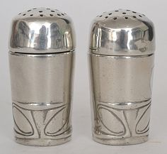 Archibald KNOX - LIBERTY & Co - A pair of polished pewter cylindrical pepperettes w/ stylised whiplash details below pierced covers, impressed 0347 to base. (hva)