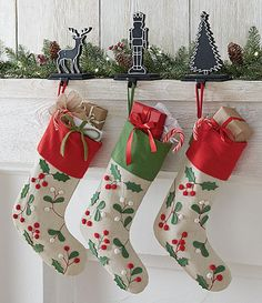 Pretty stockings for the family. These 100% cotton stockings feature holly and berry appliques and a loop for hanging. This timeless look will be perfect in your holiday decor for years to come.