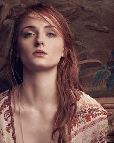 """Sophie Turner Age: 21 Height: 5'9""""  Style Loose-fitting red floral blouse. Subtle makeup."""