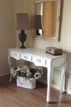 This French Provincial inspired piece displays casual elegance with its painted white finish and silver rubbed highlights on the wood details. The three drawers provide convenient storage. This versatile piece stands solid. Easy assembly of legs to to table top is required. Overall Dimensions @ widest and highest points: 44w x 20d x 30h  All of my offerings are vintage or gently used furnishings, so expect normal wear such as nicks and scratches on the wood surfaces. Furnishings are selected…
