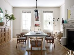 In the dining room, a Veere Grenney Assoc. light fixture is suspended above a Mecox table | archdigest.com