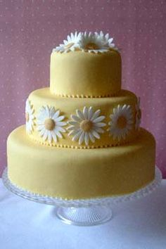 Three tier yellow fondant cake decorated with hand made gum past white and yellow daisies