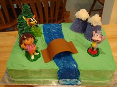 Dora Birthday Cake - Dora themed birthday cake for a little girl at a local shelter.  Figures are toys, the bridge is fondant, and the mountains and trees are decorated ice cream cones.  Thanks for looking!