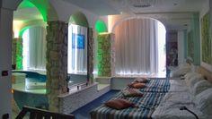 """Esto es el dormitorio de Nicole y Eva. Es un habitación espaciosa y grande. Hay 2 camas matrimoniales juntas. En frente de las camas hay una piscina hidromasaje entre vidrios y columnas de piedra con luces que crean un ambiente muy intimo. La pared es blanca y hay 3 ventanas. En frente de las camas hay una tele """"touch screen"""" dentro de un gran vidrio."""