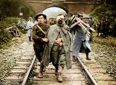 A Boche prisoner, wounded and muddy is led along a railway track as British Army infantrymen return from another push on the battlefield