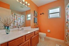 4621 Paladin Circle Vero Beach Florida 32967 Single Family Home for Sales - Listed by Brad Shearer, Bath with orange walls, wood cabinets, and bright lighting.