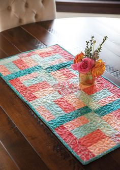 Strip piece your way to a springy, coral and turquoise batik table runner. This table runner can be finished in a single day.