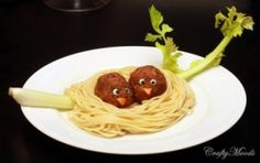 Cute food: little birdie meat balls in a spaghetti nest on a celery branch.