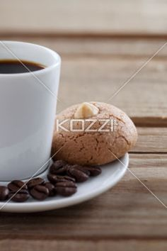coffee cup with beans and cookie - Close-up shot of coffee drink with beans and cookie on saucer