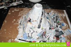 Volcano Science Experiment - Add strips of newspaper dipped into paper mache