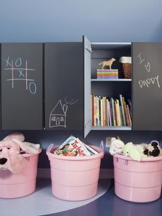 Chalkboard cabinets and plastic bins for storage in kid's room.