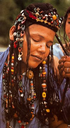 Hair decoration is beloved by Mauritanian women. This fantastic example is out of Angela Fisher's Africa Adorned book. Here her plaits are embellished with pendants, carved shell discs, triangular tailsmen, glass beads, carnelian and amber beads. We Are The World, People Around The World, Curly Hair Styles, Natural Hair Styles, Updo Curly, African Tribes, African Art, Hair Decorations, African Culture