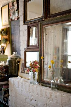 Above the expose brick fire place. Brown vintage photo frame mirrors with outdoor picked flowers in glass jars.