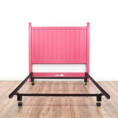 This full-sized bedframe is featured in a wood with a fuschia pink paint finish. This contemporary style bed has a black metal base, round finial tops, and slatted headboard. An adorable addition to any room! #contemporary #beds #bedframe #sandiegovintage #vintagefurniture