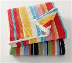 This is a knitted blanket suitable for both girls and boys having bold multi colours. These colours are contrasted well with white stripes in between and a white knitted border.