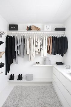 15 Minimalist Hacks To Maximize Your Life -- Start cleaning and organizing now to achieve the minimalist closet of your dreams! Love this all-white walk-in closet with a gray shag rug and dresser with wall shoe rack, perfect for a stylish storage solution.