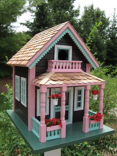 In the Northern Michigan resort town of Petoskey, you'll find some of the most delightful summer cottages. Our birdhouse, embellished with hanging flower baskets and topped with a rich western red ce