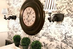 What's more french than classic black and white toile mixed with coordinating decor, wrought iron sconces and touches of greenery. Love this!
