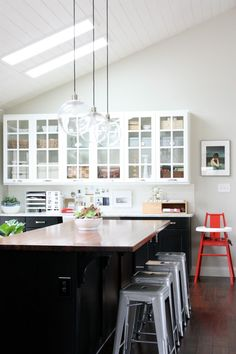 the lights, the glass front cabinets, black island. I love all the clean lines and color contrast