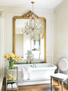 I love everything about this bathroom...the flowers, the chandelier and that huge mirror!