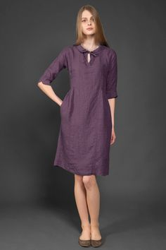 """Dark aubergine purple linen dress with a Peter Pan collar that can be tied into a bow to create a """"keyhole"""" neckline. The sides just above the waist are slightly pleated. It also features 3/4 length sleeves with slits at the cuffs, and comfortable side pockets. This loose-fitting knee-length dress is made from specially washed fabric, making it really soft and shrink-resistant. A sophisticated yet casual garment for just about any occasion. // €85"""