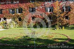 Photo taken inside the park that is in the back of the castle of Strassoldo Friuli (Italy). In the image you see, in the meadow, a small table and chairs in metal filled with apples, as it is across the lawn in a wide circumference obtained with the leaves.It is the background of the castle facade covered in ivy with red leaves.