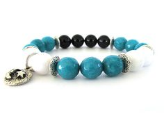 Beautiful womens charm bracelet with 10mm turquoise and white faceted and round jade beads, 10mm black onyx beads and pewter accent beads as well as pewter moon and star charm. The beads blend seamlessly and are reminiscent of a romantic, nighttime sky ... . A stunning womens bracelet that is a wonderful gift to give. Bracelet measures 7 to 7 1/4 and is strung on durable clear stretch jewelry cord for a one size fits most style. Unsure about your wrist size? Check out our Bracelet Sizin...